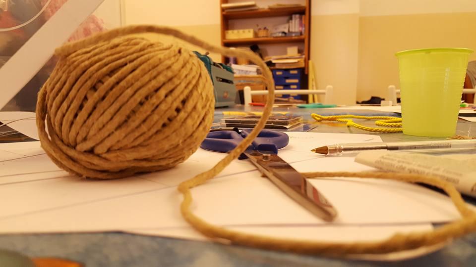tavolo su cui poggia un gomitolo di lana e un paio di forbici