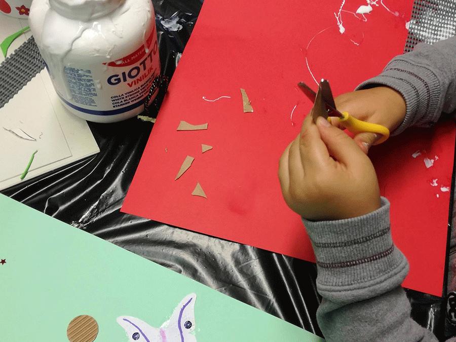 bambino che ritaglia un cartoncino con la forbice